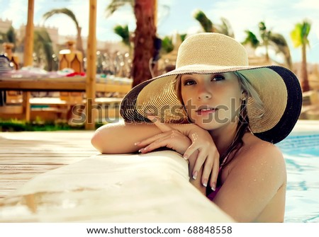 The smart blonde in a hat in pool of expensive hotel - stock photo
