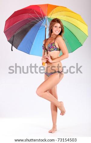 The smile girl in bikini with a multi-coloured umbrella