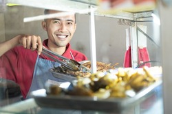 The smiling Asian male waiter takes the fried chicken on the iron tray in the food stall display window