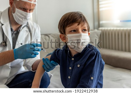 The smiling boy is looking away while his doctor holding a syringe next to his arm. Pediatrician makes vaccination to cute Caucasian boy. Boy in medical face mask getting flu shot by doctor at home.