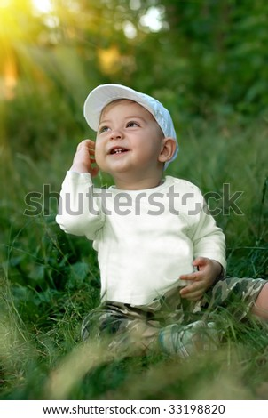 The smiling boy sits on a grass under sun beams