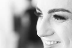 The smiling face of a girl close-up during the make-up. Focus on near eye. Shallow depth of field.B/W photo