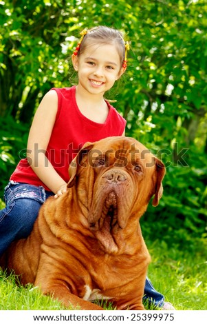 The smiling girl astride the big dog of breed FRENCH MASTIFF, DOGUE DE BORDEAUX