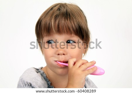 The smiling girl brushes teeth