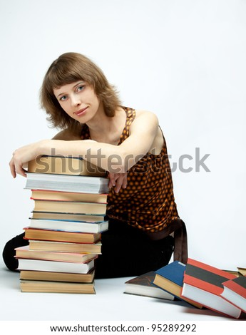 The smiling girl sitting among books on the floor; neutral background