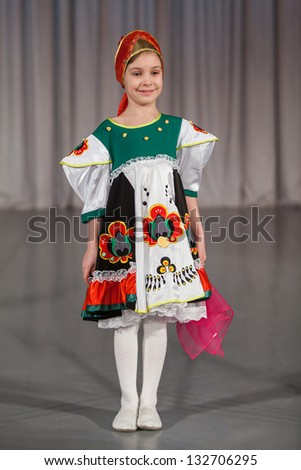 The smiling little girl in folk costume with red wrap performs on stage.