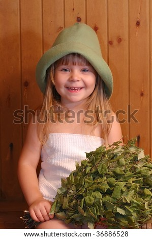 The smiling little girl with a broom in a sauna
