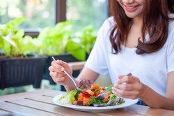 The smiling woman enjoys eating a salmon salad. To lose weight and diet, eat foods that are beneficial to the body. Weight loss concept.