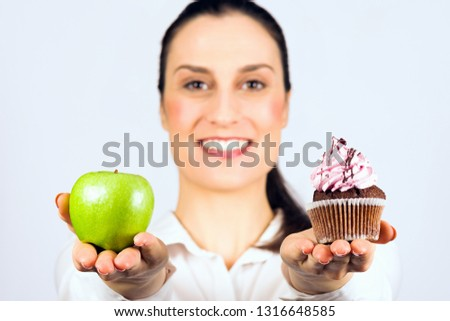 The smiling woman gives a choice to deciding apple or cupcake, healthy or unhealthy eating. #1316648585