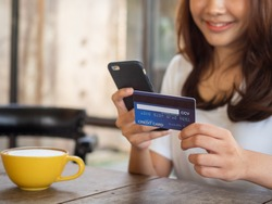 The smiling young Asian woman enjoys shopping online via a smartphone and paying online via credit card. Convenience of spending without cash. stay safe, shopping from home and Social distance