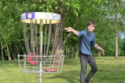 The smiling young man throws the disc golf disc