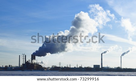 The smoke goes from factory's pipes in the snow field