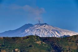 the smoking Etna Volcano a few days after an eruption, seen from the Peloritani Mountains
