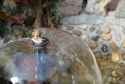 The snail climbed the fountain pillar and enjoyed the water.