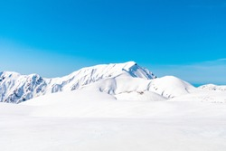 The snow mountains wall of Tateyama Kurobe alpine or japan alps in sunshine day with  blue sky background is one of the most important and popular natural place in Toyama Prefecture, Japan.
