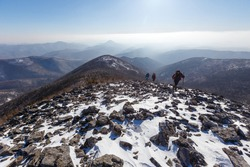 The snowy peaks of the Sestra mountain in the Lazovsky district of the Primorsky Territory. Tourists walk along the ridge of a rocky mountain against the backdrop of other mountains in winter