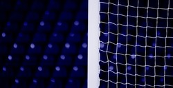 The soccer field view through white square gate net. Football sport background. Blue color background