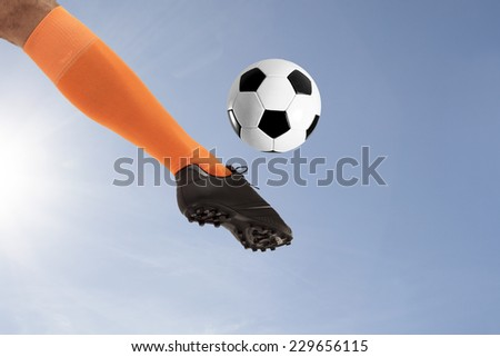 The soccer foot kicking ball on sky background