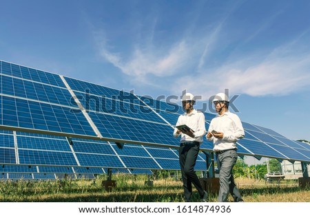 The solar farm(solar panel) with two engineers walk to check the operation of the system, Alternative energy to conserve the world's energy, Photovoltaic module idea for clean energy production. Stockfoto ©
