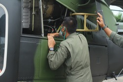 The soldier checks the aircraft engine before taking off.