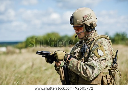 The soldier  in full gear reloads a gun