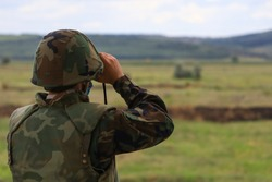 The soldier looks through binoculars. Back view, selective focus and blurred green nature background.