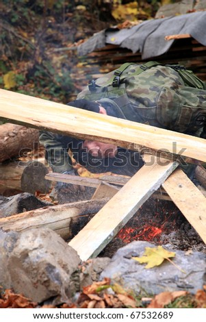 The soldier resting after the patrol is lighting a bonfire on the militarycamp.