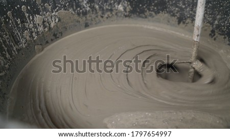The solution is in a bucket. fresh wet grout inside a bucket close-up. Macro shot of a mortar in a bucket. Stockfoto ©