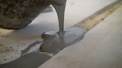 The solution is poured into the gap in the floor. dark bucket. Floor leveling solution. A bucket from which the mortar is poured. Seal the hole in the floor with mortar.