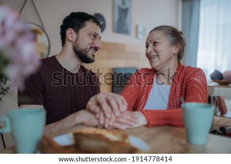 The son congratulates his mother on the holiday, a family feast. An adult son cheerfully drinks tea with an elderly beautiful mother in the kitchen. A man visiting his beloved mother on a holiday