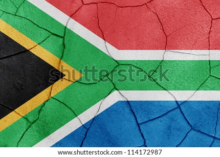 The South Africa flag painted on a cracked desert ground surface - stock photo