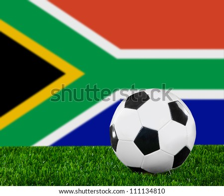 The South African Republic flag and soccer ball on the green grass