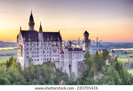 The South side of the Neuschwanstein castle photographed at sunset on a summer afternoon with soft pastel colors in the sky.