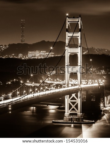 The South tower of Golden Gate Bridge at night in black and white.