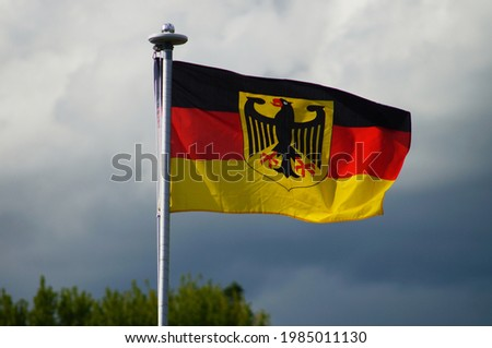 The sovereign flag of the Federal Republic of Germany flies in a garden  Private use with the federal eagle is prohibited but tolerated  Stormy sky  ストックフォト ©