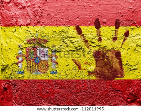 The Spanish flag painted on grunge wall with bloody palmprint over it