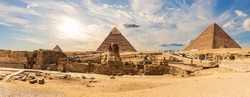 The Sphinx in front of the Great Pyramids of Giza  near the ruins of a temple in Egypt