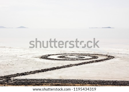 The Spiral Jetty extends into the northern end of the Great Salt Lake in Utah. Clouds overhead blend with the water of the lake in a grey layer interupted by Antelope Island in the background. #1195434319