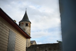 The spire of an old stone clock tower against dramatic cloudy blue sky. Architecture of Scandinavia. Travel destinations, landmarks, sightseeing, culture, architecture, exterior, history, past