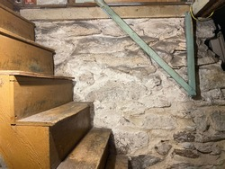 The spooky staircase to the cellar in an old house, with stone foundation.