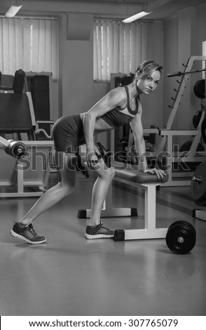 The sports girl with weights in the gym. Work on the body. Training and training of professional bodybuilder. Beautiful blonde with sports equipment.