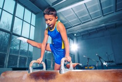 The sportsman performing difficult gymnastic exercise at gym. The sport, exercise, gymnast, health, training, athlete concept. Caucasian fit little boy