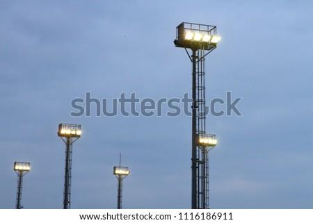 The spotlight illuminate the stadium on the cloudy evening. #1116186911