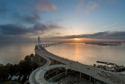 The sprialing off ramps of the new San Francisco Oakland Bay Bridge in the foreground of the Bay at Sunrise