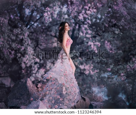 The spring fairy stands on the background of a flowering, rosy tree. She wears a pink dress with flowers that flutters in the wind, emphasizing a sexy silhouette and long legs. Art photo
