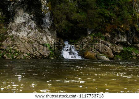 The spring follows a waterfall from the rock and flows into the river on a precipitous river bank #1117753718