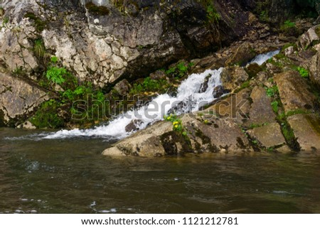 The spring follows a waterfall from the rock and flows into the river on a precipitous river bank #1121212781