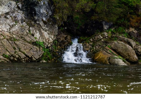 The spring follows a waterfall from the rock and flows into the river on a precipitous river bank #1121212787