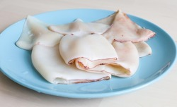 the squid carcass lies on a plate on the table. Proper nutrition, protein, seafood, affordable squid meat, raw food diet