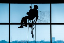 The staff is using a rope to rappelled down to clean the dirty glass of an airport building. Silhouette cool tone concept.